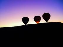 Silhouette des ballons à air chauds volant au-dessus de la vallée de Cappadocia Photographie stock libre de droits