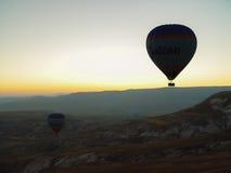 Silhouette des ballons à air chauds volant au-dessus de la vallée de Cappadocia Photo stock