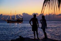 Silhouette des couples à la plage pendant le coucher du soleil Concept de vacances photographie stock