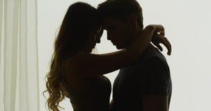 Silhouette des couples étant intimes devant la fenêtre Photographie stock libre de droits