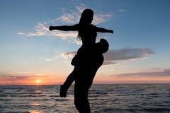 Silhouette des couples affectueux à la plage pendant le coucher du soleil Images libres de droits