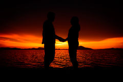 Silhouette des couples au lever de soleil Photos stock