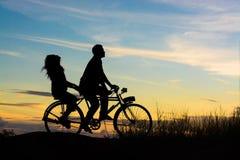Silhouette des couples conduisant le coucher du soleil heureux de temps de vélo Photos libres de droits