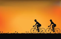 Silhouette des couples conduisant le vélo avec le beau ciel au coucher du soleil Photos libres de droits