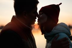 Silhouette des couples d'amants sur le coucher du soleil par le lac Sun entre les profils de personnes Ciel de crépuscule, l'eau  Photographie stock
