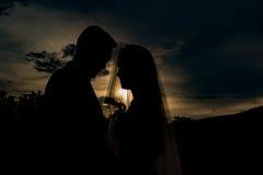 Silhouette des couples de mariage dans le beau coucher du soleil Image libre de droits