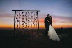 Silhouette des couples de mariage sur le fond de l'événement Photos stock
