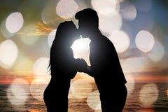 Silhouette des couples embrassant à la plage pendant le coucher du soleil Image stock