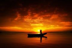Silhouette des couples embrassant dans le coucher du soleil Photographie stock