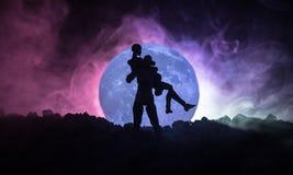 Silhouette des couples embrassant sous la pleine lune Main de fille de baiser de type sur le fond de silhouette de pleine lune Co Images libres de droits