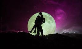 Silhouette des couples embrassant sous la pleine lune Main de fille de baiser de type sur le fond de silhouette de pleine lune Co Photos stock