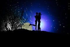 Silhouette des couples embrassant sous la pleine lune Main de fille de baiser de type sur le fond de silhouette de pleine lune Co Photo libre de droits