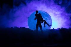 Silhouette des couples embrassant sous la pleine lune Main de fille de baiser de type sur le fond de silhouette de pleine lune Co Photographie stock libre de droits