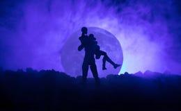 Silhouette des couples embrassant sous la pleine lune Main de fille de baiser de type sur le fond de silhouette de pleine lune Co Photographie stock
