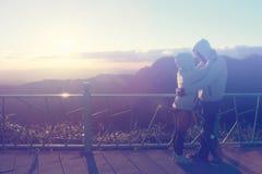 Silhouette des couples heureux au brouillard et au soleil scéniques de montagne Photo stock