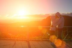 Silhouette des couples heureux au brouillard et au soleil scéniques de montagne image libre de droits
