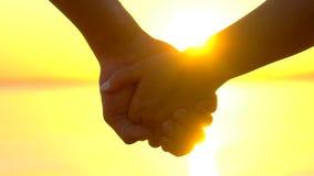 Silhouette des couples heureux romantiques, de deux amants, du jeune homme et de la femme tenant des mains au rivage d'océan au c banque de vidéos