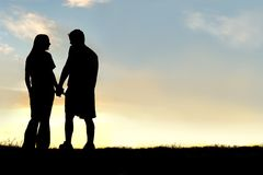 Silhouette des couples heureux tenant des mains et parlant au coucher du soleil photographie stock libre de droits
