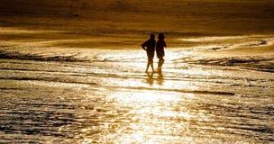 Silhouette des couples marchant sur la plage dans le coucher du soleil Photographie stock