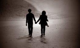 Silhouette des couples marchant sur une plage. Photos stock