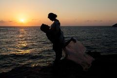 Silhouette des couples par la mer Photographie stock libre de droits