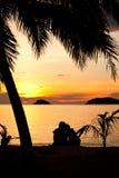 Silhouette des couples romantiques se reposant sur une plage Image libre de droits