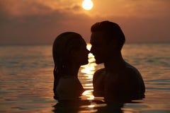 Silhouette des couples romantiques se tenant en mer Image stock