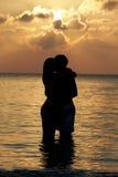 Silhouette des couples romantiques se tenant en mer Photo stock