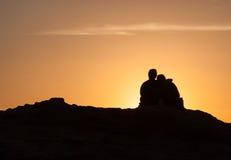 Silhouette des couples se reposant sur une roche au coucher du soleil Images libres de droits