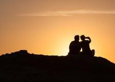Silhouette des couples se reposant sur une roche au coucher du soleil Photos libres de droits