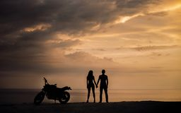 Silhouette des couples se tenant avec une motocyclette dans le coucher du soleil image stock