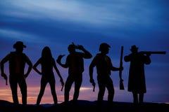 Silhouette des cowboys dans le coucher du soleil avec des armes à feu Images stock