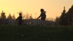 Silhouette des enfants courant au coucher du soleil clips vidéos