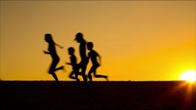 Silhouette des enfants courants contre le coucher du soleil banque de vidéos