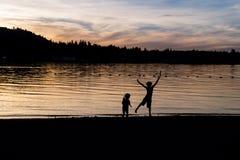 Silhouette des enfants dansant sur la plage au crépuscule Photos stock