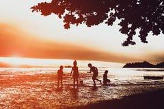 Silhouette des enfants jouant à la plage pendant le coucher du soleil au KOH Image stock