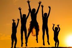 Silhouette des enfants sautants contre le coucher du soleil Photo libre de droits