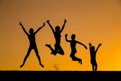 Silhouette des enfants sautants contre le coucher du soleil Images libres de droits