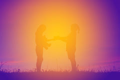 Silhouette des enfants tenant le boîte-cadeau au coucher du soleil de ciel Image stock