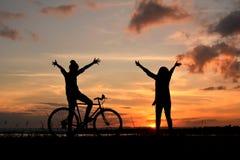 Silhouette des femmes heureuses avec les mains ouvertes de bicyclette Photographie stock