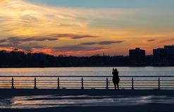 Silhouette des femmes photographiant le coucher du soleil à New York City photo stock
