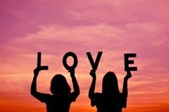Silhouette des femmes tenant le mot d'amour Photos libres de droits