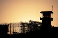 Silhouette des fils et du tour de guet barbelés de la prison photos stock