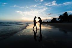 Silhouette des frères tenant des mains sur la plage Images libres de droits