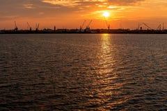 Silhouette des grues de port maritime au lever de soleil Chioggia, Italie Photos stock