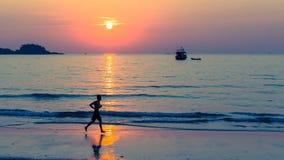 Silhouette des hommes courant sur la côte Image stock