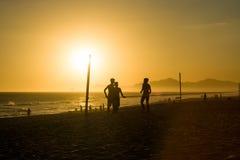 Silhouette des hommes parlant à la plage pendant le coucher du soleil à Rio de J Image libre de droits