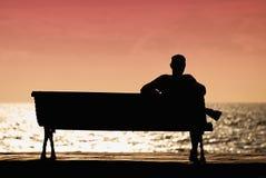 Silhouette des hommes seul s'asseyant sur le banc photographie stock