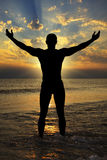 Silhouette des hommes sportifs vers la mer au coucher du soleil Image libre de droits