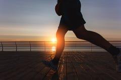 Silhouette des jambes masculines qui fonctionnent à l'aube au-dessus de la mer Photo libre de droits